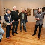 Collection Transition Assistant Ben Davis talks to visitors about his exhibition Pale Rider.