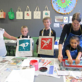 Waitotara Principal Jane Corcoran with pupils Bruce Butters-Fitton and Cooper Mackintosh displaying their completed tote bags while Sarjeant educator Sietske Jansma assists Kimberley Frewin with the screen printing process.